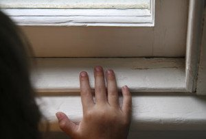 Hand resting on a windowsill