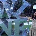 Woman posing by a statue of tilted letters